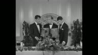 CU Dean Martin and Jerry Lewis hold Box Office award plaques in front of their faces lower them and Lewis speaks / they stand at podium with...