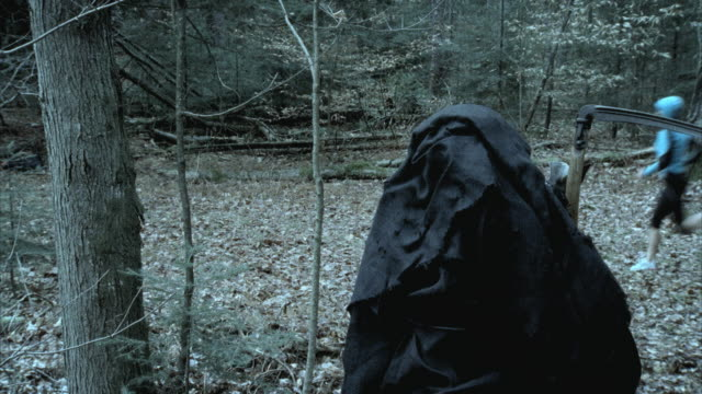 MS Death figure in foreground watches woman running and stopping in woods, Morrisville, Vermont, USA