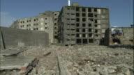 Debris surrounds abandoned buildings on the uninhabited Hashima Island in Nagasaki, Japan.
