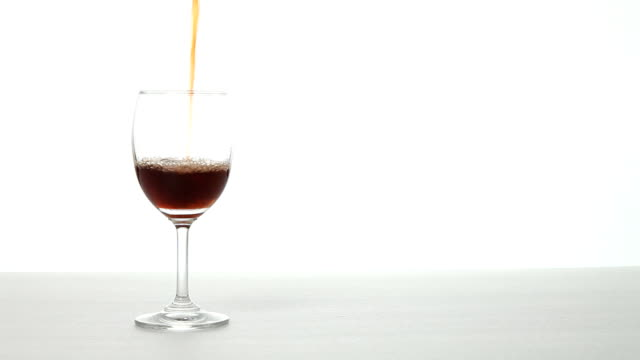 Decant red wine into a glass on white background