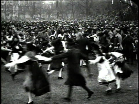 December 1918 WS large groups of people in traditional Alsatian dress holding hands and dancing in a circle to celebrate an Allied victory after WWI...