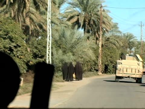 December 27 2003 WS POV Three women wearing burkas walking down street Baghdad Iraq AUDIO