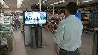 December 8 2010 MS Customer watching instore display of flatscreen television in Micro Center / United States