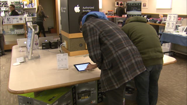 December 8 2010 HA Customers viewing ereader program on iPad and flicking through ebook pages at Micro Center instore Macintosh display / United...