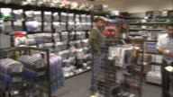 December 8 2010 PAN Sales clerk assisting customers beside shelves of technical wiring and components at Micro Center / United States