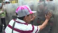 Decenas de personas chocaron con policias el miercoles en Caracas molestos por la escasez de alimentos cuando esperaban en las afueras de un...