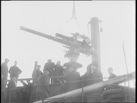 Deck of merchant ship / montage of lowering moving gun onto a ship / Capital Building Washington DC / people in hallway Congress in session / Speaker...