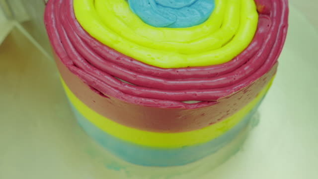 Decorate cake with colorful butter cream. Front view. Close up. Time lapse.