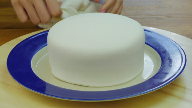 Decorate the cake with Fondant flowers. Front view. Time lapse.