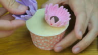 Decorate the cupcake with Fondant flowers. Front view.