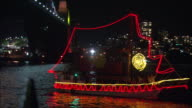 Decorated boats travel across Sydney Harbor during a New Year's Eve celebration.