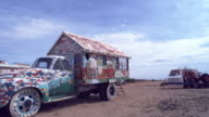 MS,  Decorated house on back of pick-up truck on field, Niland, California, USA