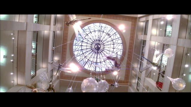 PAN Decorations hanging from circular glass window in multi level shopping mall