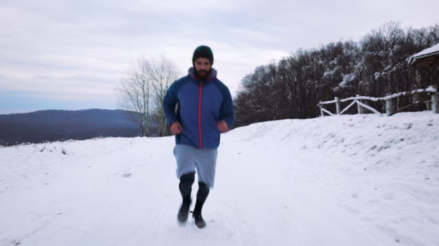 Dedicated male athlete jogging on a snow.
