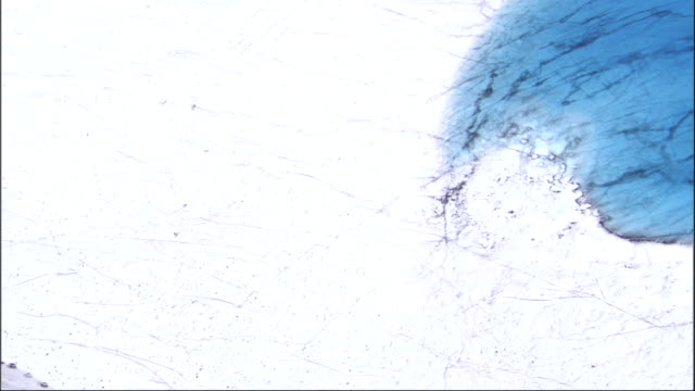 Deep blue water collects on the surface of a glacier. Available in HD.