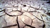 Deep cracks spread across the desert floor. Available in HD.
