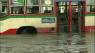 Deep flood water surrounds a Bangkok bus
