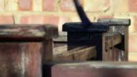 Deep Focus Shot of Varnishing a Wooden Post