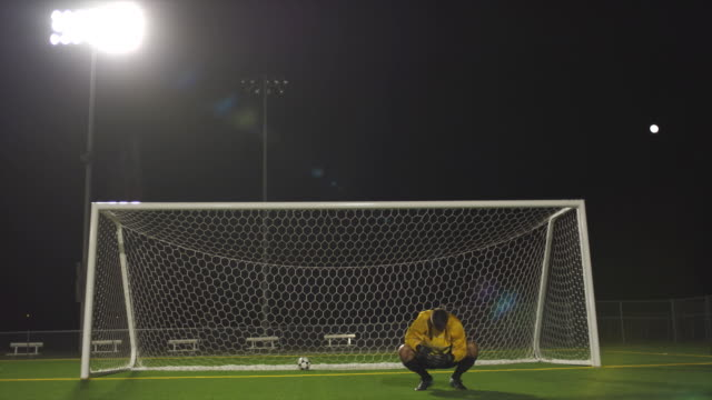A soccer team celebrates their victory while the goalie of the opposing team crouches in disappointment.