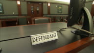 A defendant placard occupies a courtroom table.