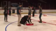 WGN Defenseman Trevor van Riemsdyk assists crew members in painting the Indian head logo and line on the Chicago Blackhawks' home ice rink at the...