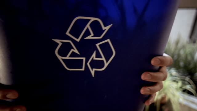CU defocus PORTRAIT man holding recycling bin full of shredded paper/ man setting paper down/ New York City