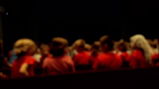 Defocused child audience in theater premiere