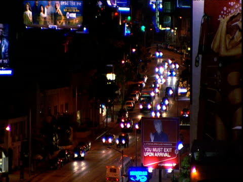 Defocused lights of traffic on sunset strip traffic including white limousine track from car past Chateau Marmont sign neon signs for Roxy and Rainbow nightclubs Los Angeles