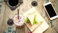Delicious bologna whole wheat sandwich with iced chocolate and smartphone on wooden table. View from above.