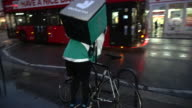 A Deliveroo courier leaves a restaurant with a takeaway delivery ABSA627D