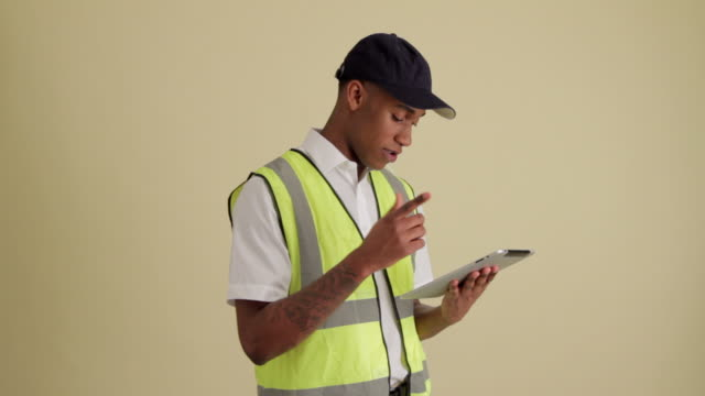 MWS delivery driver profile  using tablet looking up at camera and smiling