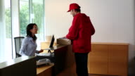 MS ZI Delivery man giving box to receptionist  / Brussels , Brabant, Belgium