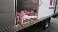 A delivery man moves half a slaughtered pig out of a truck onto a trolley Pig entrails are unhooked from inside a truck for delivery to a butcher An...