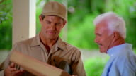 MS delivery man scanning package + middle-aged man signing for package