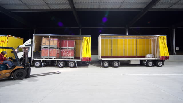 T/L WS Delivery trucks being loaded at courier center at night, Auckland, New Zealand
