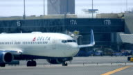 Delta airline plane with passengers arrives to LAX airport near control tower on March 17 2016 in Los Angeles California 4K from RAW / Los Angeles...