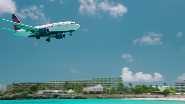 WS TS Delta Airlines flying over sea and Maho Beach / St. Maarten
