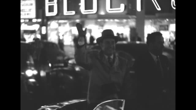 Democratic Party presidential candidate Adlai Stevenson sits in rear of convertible at night as he moves through Seattle's business district / he...