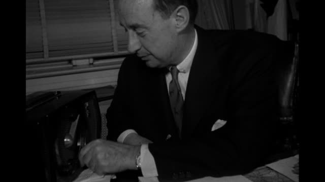 Democratic presidential candidate Adlai Stevenson II sits at desk dials radio takes notes