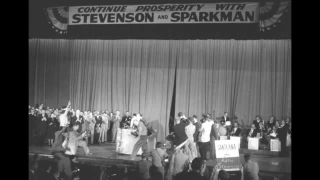 Democratic presidential candidate Adlai Stevenson walks to podium in auditorium with standing ovation from excited supporters / banner over stage...
