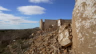 demolished walls and rubble of old stone farm house against blue sky with white clouds