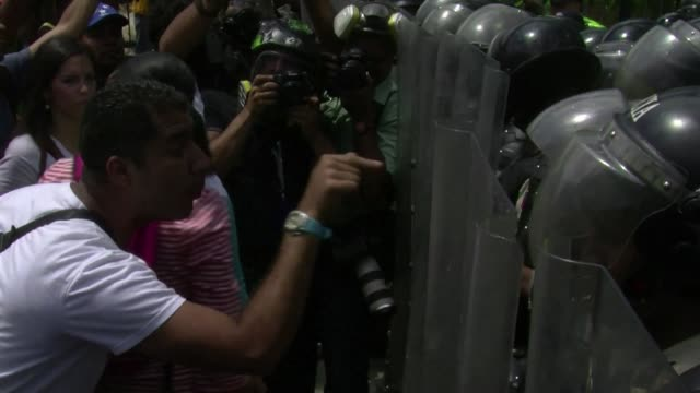 Demonstrators clashed with riot police in Caracas after a march against the arrest of two opposition mayors accused of failing to stop violence in...