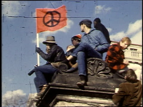 Demonstrators holding a flag on top of a monument / Washington DC United States
