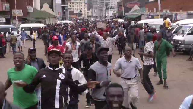 Demonstrators in Harare gather to call for embattled President Robert Mugabe to quit amid a frenzy of cheering and dancing in downtown Harare