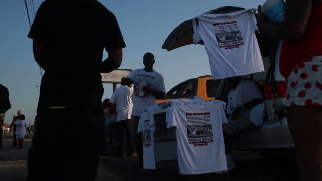 Demonstrators protest the police shooting death of Michael Brown in Ferguson Missouri US A man hands out t shirts to demonstrators joinging the...