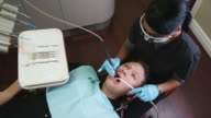 dental hygienist working on a male patient