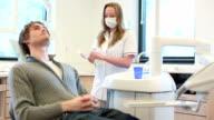 Dental preparare handgloves con paziente disteso in attesa
