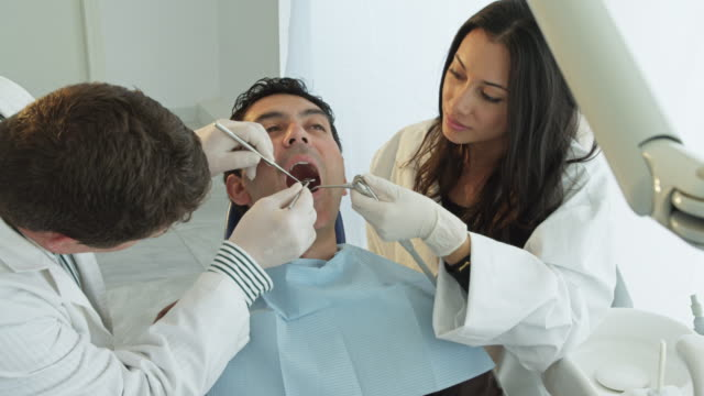 HA dentist assisted by nurse examining teeth of patient