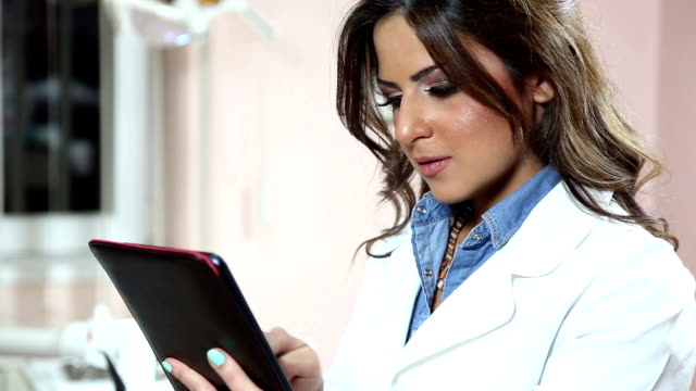 Dentist working on tablet and smiling