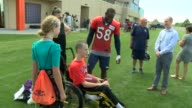 Denver Broncos linebacker Von Miller enjoys interacting with a fan after a training camp practice in which the young man in a wheelchair gets to do a...